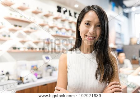 Young Woman holding business in optician shop