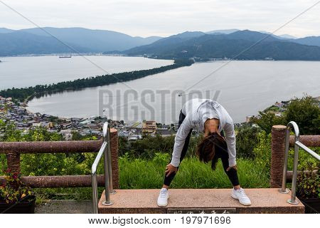 Woman viewing the landscape upside down in Amanohashidate in Kyoto