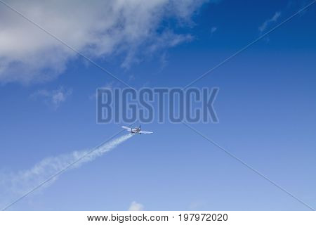 The sports plane flies away against the blue sky with white clouds