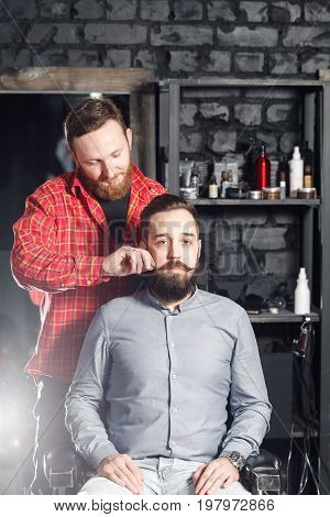 Close-up side view portrait of handsome young bearded caucasian man getting beard grooming in modern barbershop. Making beard haircut using shaver