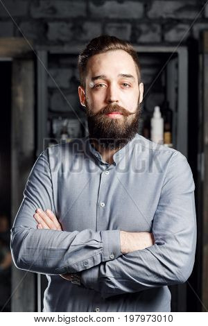 Portrait of bearded male in gray shirt. ready-cut beard and twirled moustache