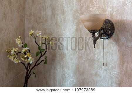 The sconce is placed on the wall and the flowers in the corner of the room