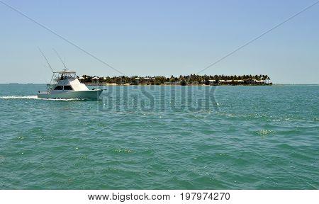 Sunset West Florida Keys Florida USA - May 15 2017 : Fishing boat sailing past Sunset Key in Florida