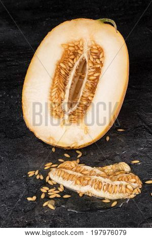 A close-up picture of a ripe yellow melon sliced in half on a black stone background. A tasteful cantaloupe melon full of nutritious seeds. Refreshing and sweet ingredients for vegetarian meals.