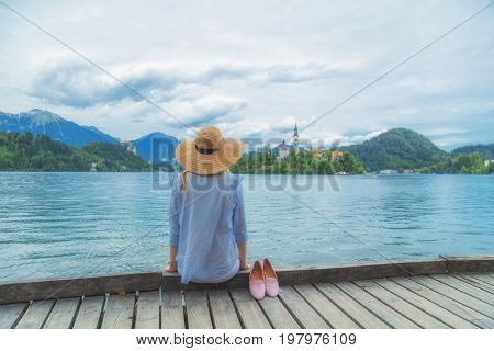 Young woman sitting on a wooden pier and enjoying the summertime.