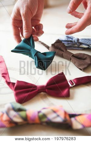 The male hand choosing hand made bow ties. Bow ties in many colors on a table