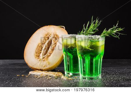 A couple of glasses filled with non-alcohol and organic cold drinks and a cut in half cantaloupe melon on a black background. Juicy melon honeydew and lime beverages with tarragon leaves on a table.