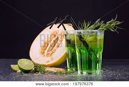 A couple of glasses filled with non-alcohol and organic cold drinks and a cut in half cantaloupe melon on a black background. Juicy melon honeydew and lime beverages with tarragon leaves and straws.