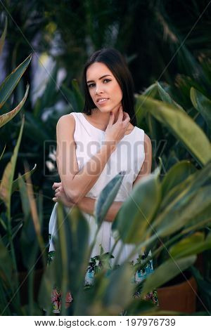 A thoughtful and confident young female on a natural tropical summer park background. A sensual woman in a stylish white dress posing in the green leaves. A glamorous and natural brunette girl.