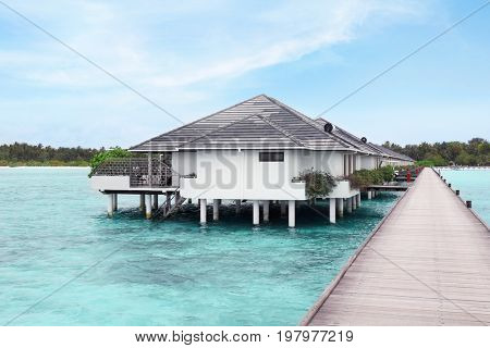 View of modern beach houses on piles at tropical resort