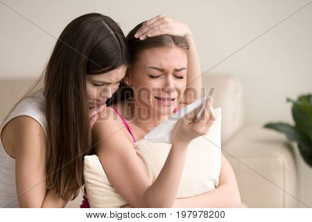 Unhappy young woman crying, wiping tears with handkerchief, her friend showing compassion and trying to appease. Friendly support in difficult time, comforting through heavy loss or emotional problems