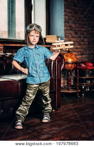 Cute dreamer boy playing with toy airplane at home. Childhood. Fantasy, imagination.