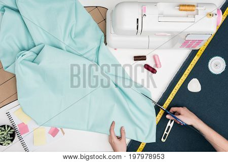 Tailor Cutting Textile With Scissors
