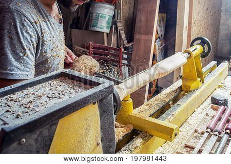 Man Makes A Wooden Product On A Lathe
