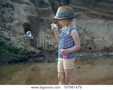 Little girl in bonnet inflates soap bubbles. The child is dirty