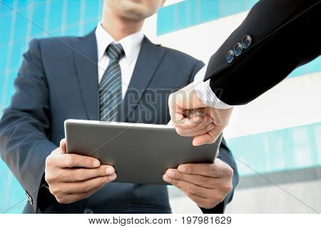 Two businessmen looking at tablet pc with one hand pointing to the screen - business discussion concept
