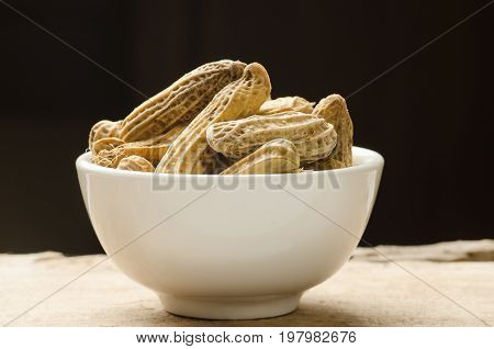 Peanuts or groundnuts in a bowl on black background