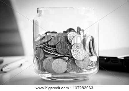 Coins in the glass jar mixed Asian multi currencies - monochrome effect