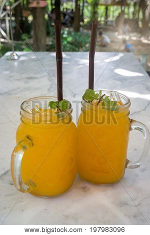 Orange juice with ice cube on marble table stock photo