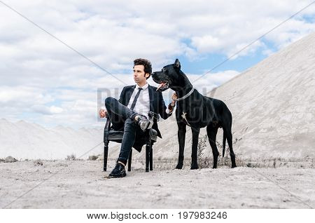 Stylish man in a black suit sits on a chair in the middle of the desert with a big dog. The concept of a successful and style