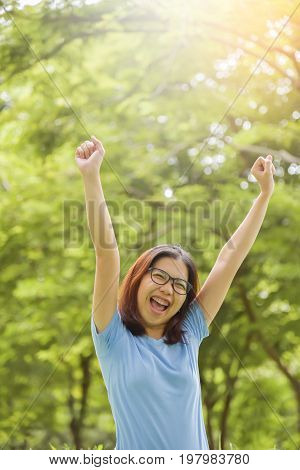 Happy Young Asian woman in Glasses celebrating with arms raised up above her head at Park outdoor. Smiling face. Freedom or success concept.
