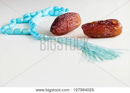 Two Fresh Dates Medjool And Rosary On White Table Background. Copy Space.