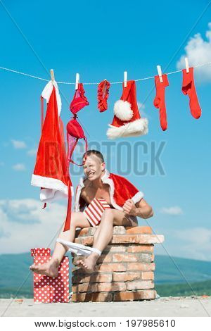 Bad santa claus at clothes for drying on chimney. Laundry and dry cleaning. Xmas red costume on rope with pin. Christmas man with present box. New year guy with muscular body.
