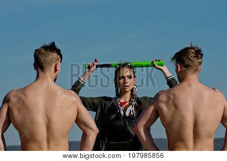 Woman with baseball bat and men. Men and sport or criminal girl outdoor. Group of people on blue sky. Beauty and fashion. Bandit gang have conflict.
