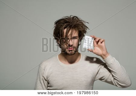 Drug and antidepressant. Man with pills in blister pack. Guy hold dieting pill or vitamin. Health and medicine.