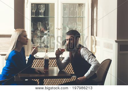 Man and woman drinking from martini glasses. Hipster and girl sharing bottle of wine in restaurant. Couple in love. Alcohol appetizer addictive and convive. Unhealthy lifestyle. Bad habits