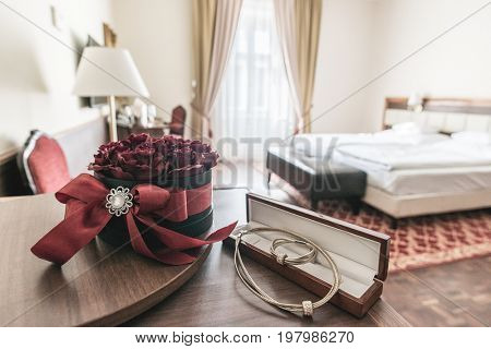 Hotel room interior. Rose decoration and diamond necklace on table as gift.