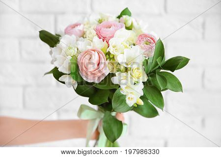 Female hand holding beautiful bouquet with freesia flowers on white brick wall background