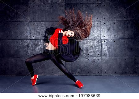 Girl dancing in front of the urban wall.