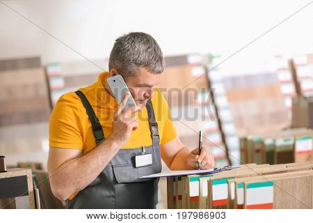 Carpenter talking on phone in hardware store
