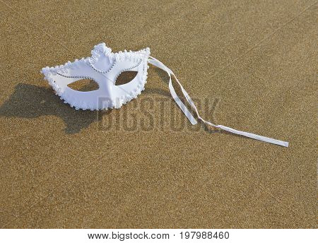 Carnival mask white color lies on the sand