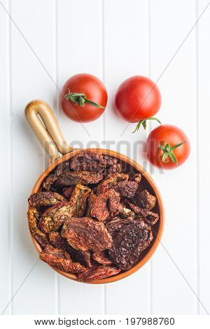 Dried sliced tomatoes in bowl and fresh tomatoes. Tomatoes as superfood. Top view.
