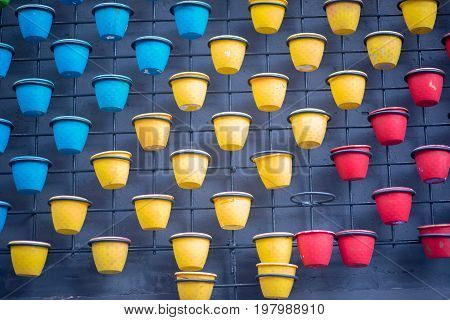 colorful plastic flower pots on wall background