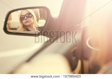Blond woman in sunglasses looking in the car rear view mirror