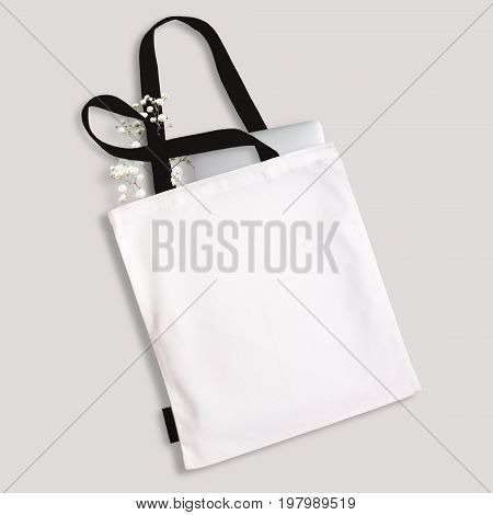 White blank cotton eco tote bag with black straps handles and little label laptop and flowers inside. Design mockup.