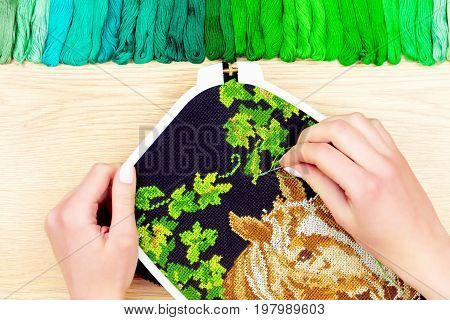 Palette of sewing threads isolated on wooden background.Female hand embroidering cross on the black canvas.