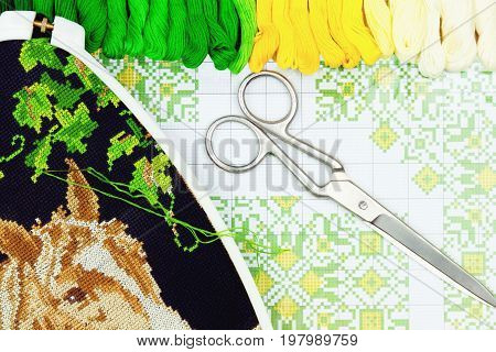 Palette of sewing threads scissors and hoop isolated on wooden background.