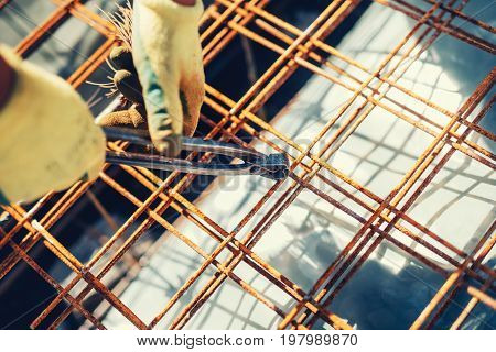 Construction Site Details With Worker Using Wire Rod And Pliers For Securing Reinforcement Steel Bar