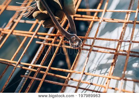 Details Of Infrastructure - Construction Worker Hands Securing Steel Bars With Wire Rod For Cement R
