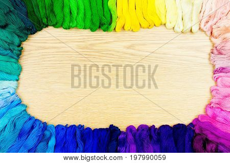 Palette of sewing threads isolated on wooden background.