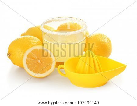 Fresh lemons, squeezer and glass of juice on white background