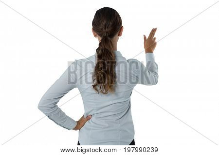 Rear view of female executive pressing an invisible virtual screen against white background