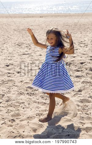 baby girl with long hair in striped blue dress running on the beach