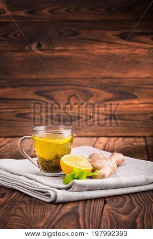 A close-up of a glass tea cup full of green tea on a wooden background. A little cup of hot and healthy beverage next to ginger and cut lemon on gray fabric. Winter organic beverage. Copy space.