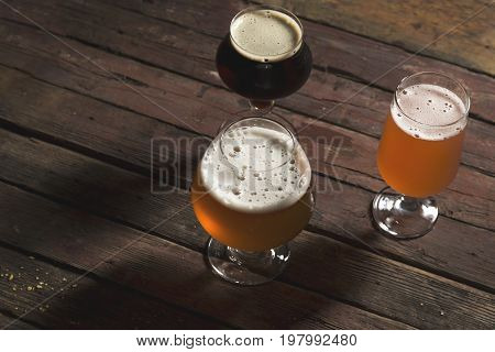 Detail of pale dark and red fruit beer in three different beer glasses on a rustic wooden table. Focus on the glass of pale beer