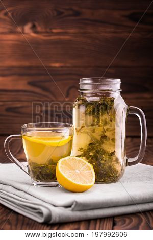 Close-up of a mason jar and tea cup filled with a bright natural hot beverage on a dark wooden background. Tasty and healthy drinks next to cut sour lemon on a gray fabric table cloth. Copy space.